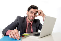 Attractive businessman at office desk working on computer laptop looking tired and busy Stock Images