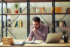 Attractive businessman reading book at home office Royalty Free Stock Images