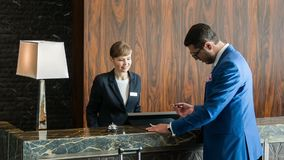 Attractive businessman registering at reception. At reception desk. New handsome visitor wearing a blue suit and black glasses standing at reception while
