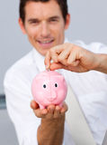 Attractive businessman saving money in a piggybank. In the office Stock Photography