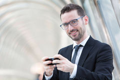Attractive Businessman sending a text during a break Royalty Free Stock Photography