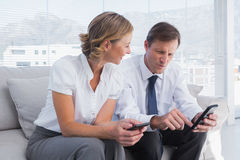 Attractive businessman showing something on his mobile phone to Royalty Free Stock Photos