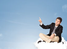 Attractive businessman sitting on cloud with copy space Stock Photo