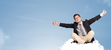 Attractive businessman sitting on cloud with copy space Stock Photos