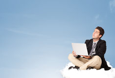Attractive businessman sitting on cloud with copy space Royalty Free Stock Photos