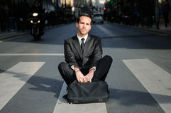 Attractive businessman sitting in a crosswalk Stock Images