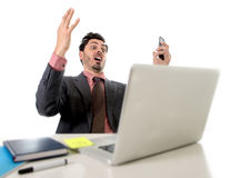 Attractive businessman sitting at office desk working in stress on computer laptop talking on mobile phone overworked Royalty Free Stock Image