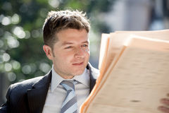 Attractive businessman sitting outdoors in breakfast pause early morning reading newspaper news looking relaxed Royalty Free Stock Photography