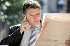Attractive businessman sitting outdoors in breakfast pause early morning reading newspaper news looking relaxed Stock Photo