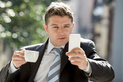 Attractive businessman sitting outdoors in coffee break using mobile phone checking onl�ne news Stock Images