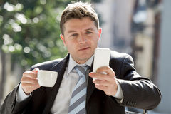 Attractive businessman sitting outdoors in coffee break using mobile phone checking onl�ne news Royalty Free Stock Photo