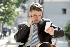 Attractive businessman sitting outdoors in coffee break using mobile phone looking thoughtful Stock Images