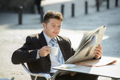 Attractive businessman sitting outdoors having coffee cup for breakfast early morning reading newspaper news looking relaxed Stock Photos