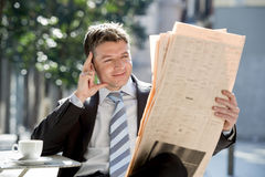 Attractive businessman sitting outdoors having coffee cup for breakfast early morning reading newspaper news looking relaxed Stock Photo