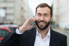 Attractive businessman smiling as he takes a call Royalty Free Stock Photos