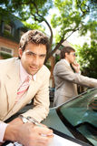 Businessmen meeting around car. Royalty Free Stock Photography