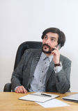 An attractive businessman speaking on his mobile at his desk in Royalty Free Stock Photo