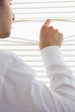 Attractive businessman spying through roller blind Royalty Free Stock Image