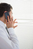 Attractive businessman spying through roller blind while phoning Stock Photos