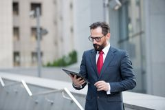 Attractive businessman in suit and red tie check or read digital tablet outdoor office building. Social communicate technology stock photos