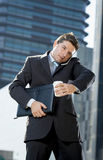 Attractive businessman talking on mobile phone outdoors with coffee and portfolio Stock Photography