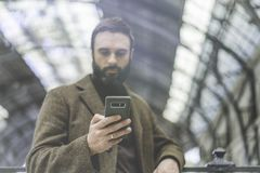 Attractive businessman texting message on his mobile phone.Casual professional entrepreneur using smartphone outside. Royalty Free Stock Photos