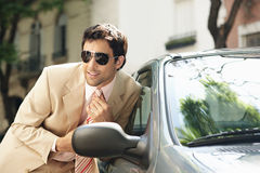Businessman grooming on car mirror. Royalty Free Stock Photo