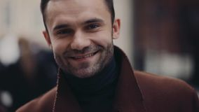 Attractive businessman walking down the crowded street, comes right to the camera and gives a bright smile. Male beauty