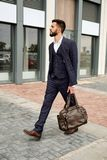 Attractive businessman walking down the street holding travel bag Stock Image