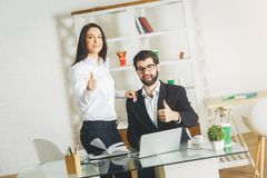 Attractive businessman and woman showing thumbs up Royalty Free Stock Images