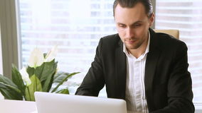 Attractive businessman working on laptop in office, looking at camera. Attractive businessman in suit using laptop in office, typing on keyboard, responding stock video
