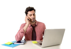 Attractive businessman working at office desk texting with mobile phone in front of computer laptop looking busy Royalty Free Stock Images