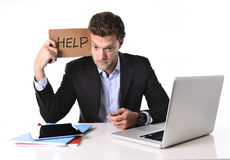 Attractive businessman working in stress at computer holding help cardboard sign Stock Images