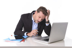 Attractive businessman working in stress at office desk computer suffering headache. Young attractive European businessman working in stress at office desk Royalty Free Stock Images