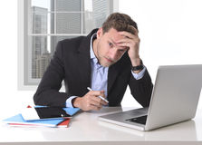 Attractive businessman working in stress at office desk computer. Young attractive European businessman working in stress at office desk computer laptop Royalty Free Stock Photography