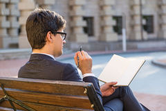 Attractive businessman writing in notepad Stock Image