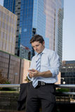 Attractive businessman writing text message at mobile phone outdoors Stock Photo