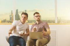 Attractive businessmen using laptop together Royalty Free Stock Photo