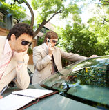 Businessmen meeting around car. Stock Images