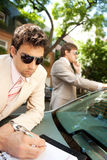 Businessmen meeting around car. Royalty Free Stock Images