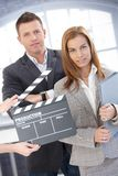 Attractive businesspeople with clapper board. During shooting a film, smiling stock photos