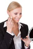 Attractive businesswoman applying foundation Stock Photography