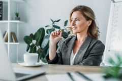 Attractive businesswoman biting glasses and looking away. In office stock photos