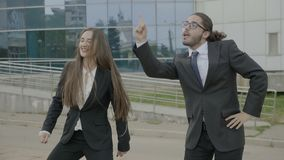 Businesswoman and business man wearing formal clothes funny dancing like crazy outside the corporation after leaving work. Attractive businesswoman and business stock footage