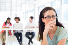 Attractive businesswoman contemplating while colleagues are in background Royalty Free Stock Images