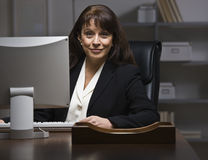 Attractive businesswoman at desk. Royalty Free Stock Image