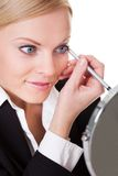 Attractive businesswoman drawing with eyeliner Royalty Free Stock Photos
