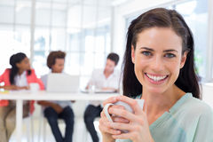 Attractive businesswoman drinking coffee with coworkers in background Royalty Free Stock Photography