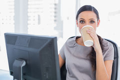 Attractive businesswoman drinking coffee and looking at camera Royalty Free Stock Photography