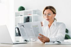 Attractive businesswoman drinking coffee and reading newspaper. In office stock photos